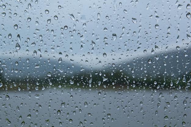 Gouttes d'eau sur les gouttes de pluie de voiture sur la fenêtre transparente