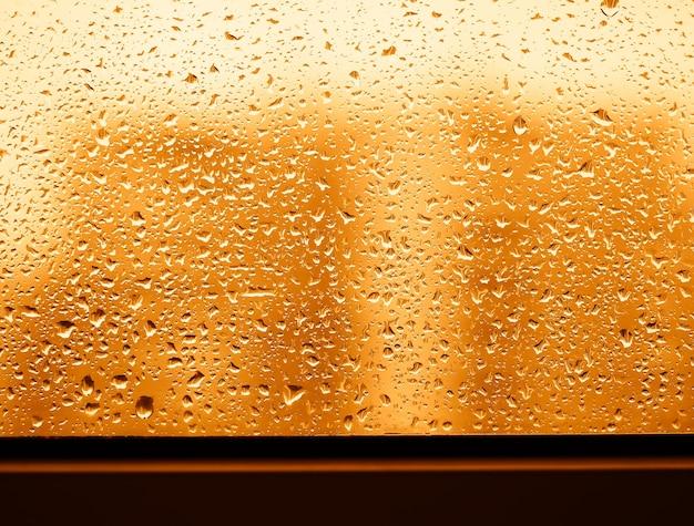 Gouttes d'eau de pluie de coucher du soleil sur le fond en verre de fenêtre