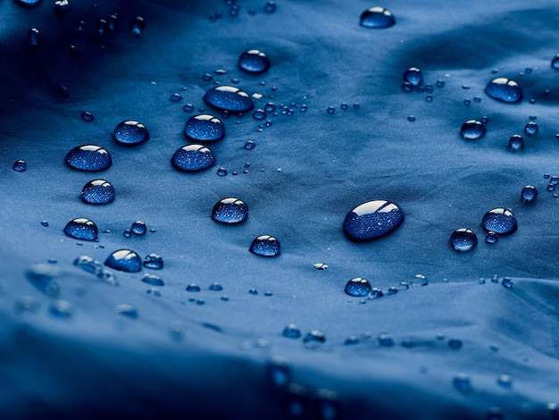 Gouttes d'eau sur le tissu de la membrane imperméable. vue détaillée de la texture du tissu imperméable bleu.