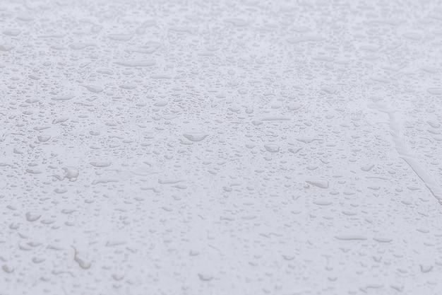 Gouttes d'eau sur la voiture. fond clair.