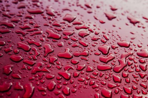 Gouttes d'eau sur une voiture rouge propre. résumé flou fond rouge. toit de voiture avec surface mouillée