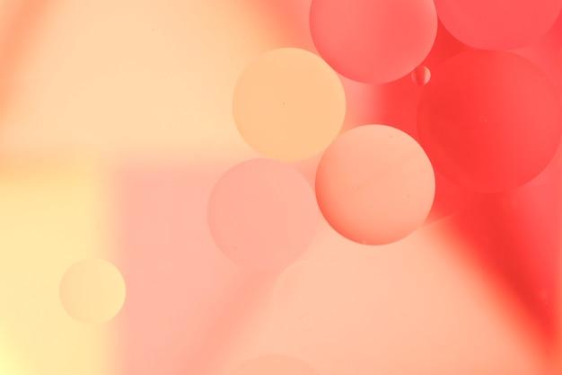 Gouttes d'huile rouge sur la surface de couleur pâle