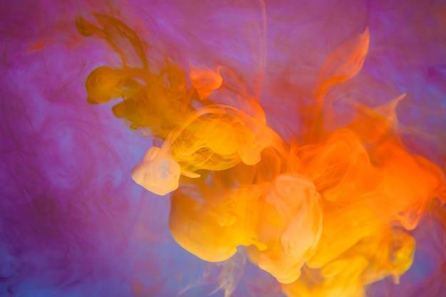 Gouttes jaune vif dans l'eau sur fond bleu