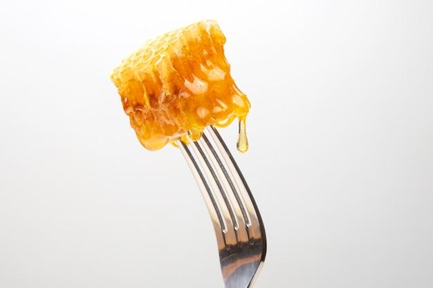 Des gouttes de miel frais coulent de miel de cire sur une fourchette de table. nutrition vitaminique et produit apicole.