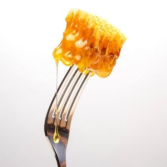 Gouttes de miel frais goutte à goutte de miel de cire sur une fourchette de table