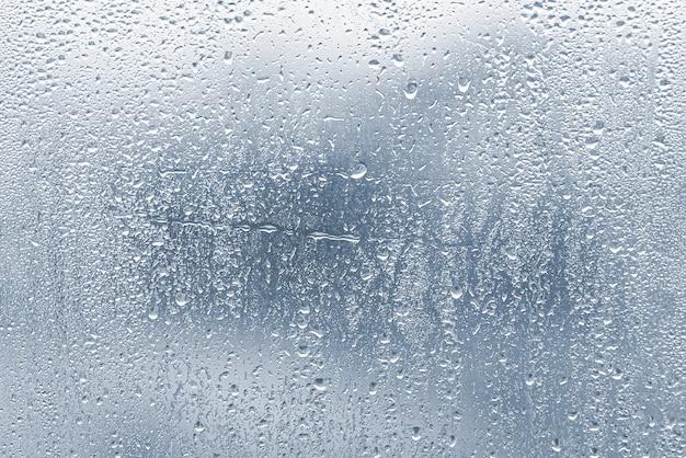 Gouttes de pluie, condensation sur la fenêtre en verre lors de fortes pluies, gouttes d'eau sur verre bleu