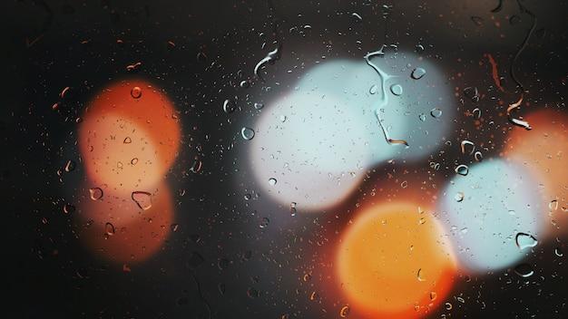 Des gouttes de pluie coulent le long du verre sur le fond bokeh des voitures en mouvement