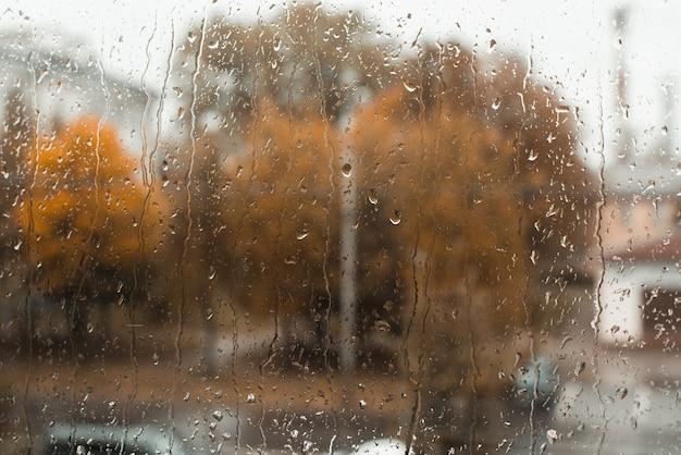 Les gouttes de pluie coulent sur la surface de la fenêtre, la ville et les arbres jaunes sont défocalisés, copiez l'espace. jour d'automne pluvieux et nuageux. notion de mauvais temps.