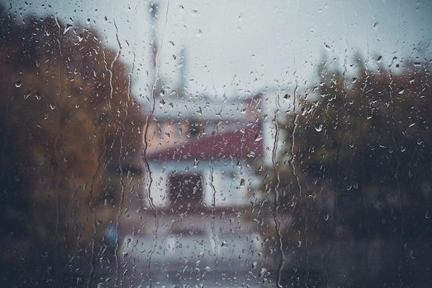 Les gouttes de pluie coulent sur le verre de la fenêtre, la rue de la ville est défocalisée, l'espace de copie. jour de pluie nuageux, concept de mauvais temps. image tonique