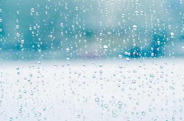 Gouttes de pluie et eau gelée sur fond de verre de fenêtre, tonification bleue