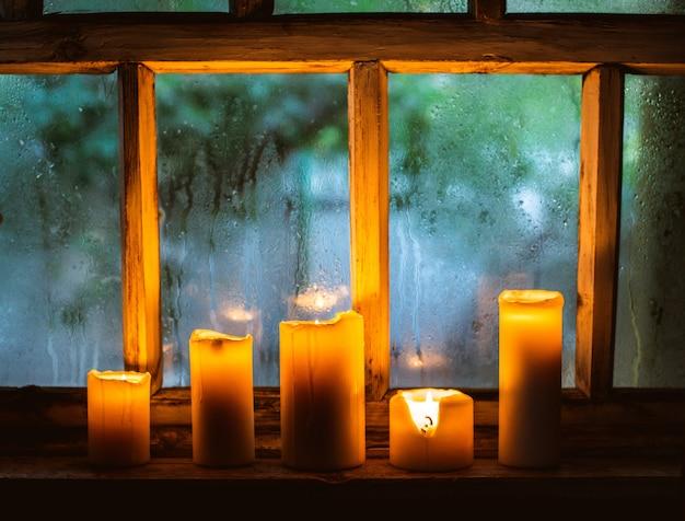 Gouttes de pluie sur la fenêtre et des bougies allumées