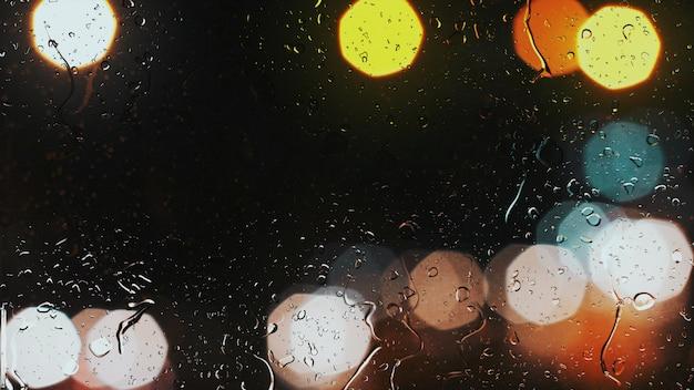 Gouttes de pluie sur une fenêtre de voiture avec un arrière-plan magnifiquement flou de feux de circulation
