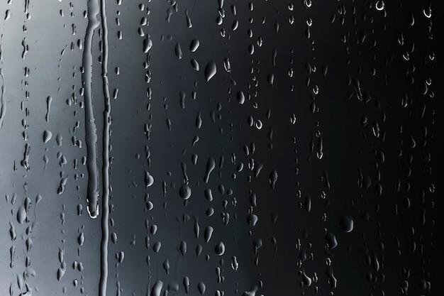 Gouttes de pluie sur fond texturé en verre