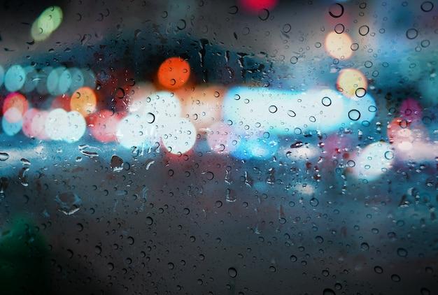 Gouttes de pluie avec lumière bokeh sur le fond de la saison des pluies route
