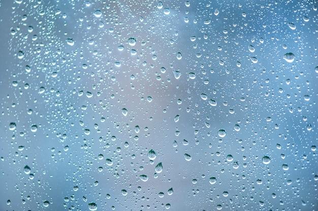 Gouttes de pluie sur verre beau fond de ciel bleu
