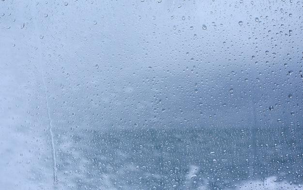 Gouttes de pluie sur le verre sur fond de mer