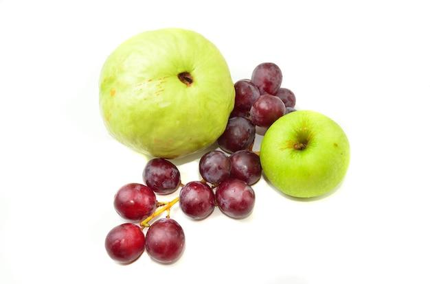 Goyave fraîche et pomme verte avec des raisins rouges isolés sur fond blanc