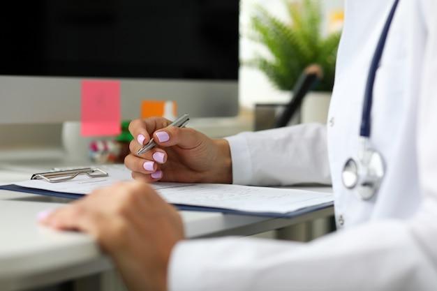 Gp prescrivant un remède assis à une table de travail