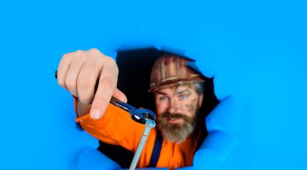 Grâce à un travailleur du papier dans un casque de protection, le constructeur détient des clés de réparation d'outils barbu