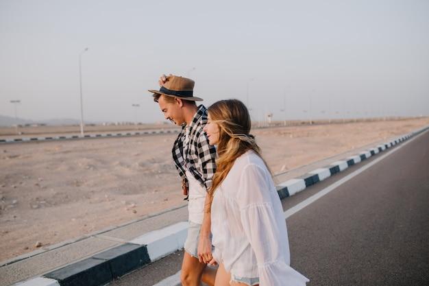 Gracieuse femme aux cheveux longs en chemise blanche et garçon au chapeau marchant sur l'autoroute, main dans la main et souriant. un couple élégant traverse la route et parle de voyages à ciel ouvert tôt le matin