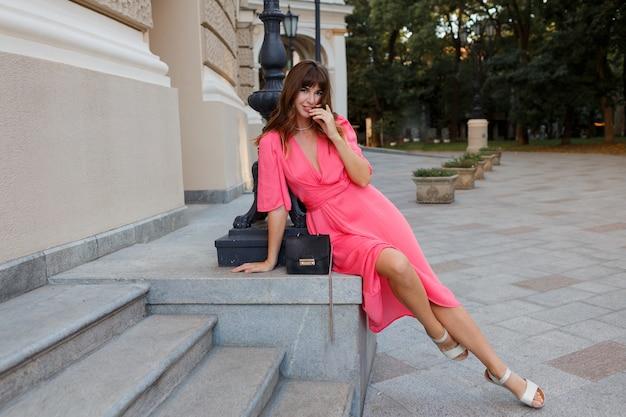 Gracieuse femme aux cheveux ondulés en robe sexy rose posant dans la vieille ville européenne. longueur totale.