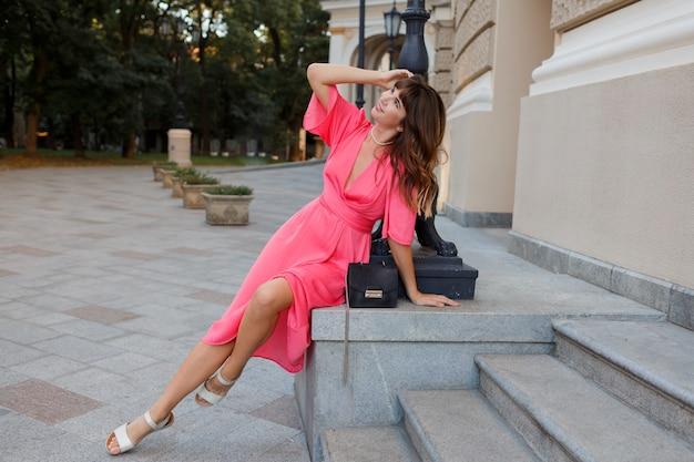 Gracieuse femme aux cheveux ondulés en robe sexy rose posant dans la vieille ville européenne.