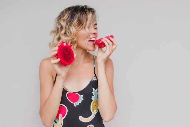 Gracieuse femme européenne mangeant du pitaya rouge avec plaisir. modèle féminin blond élégant bénéficiant de savoureux fruits du dragon.