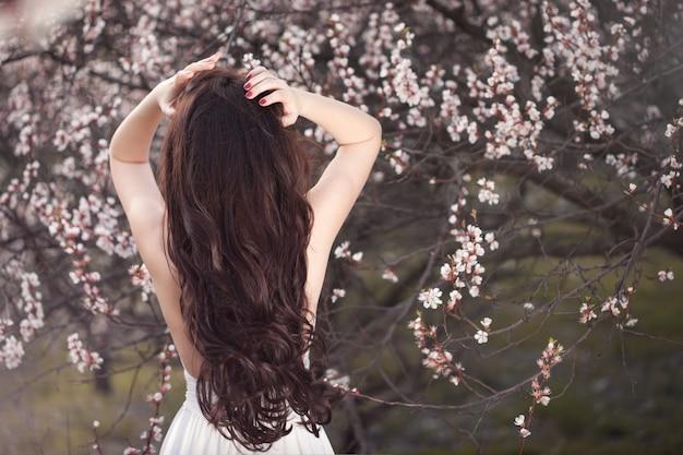 Gracieuse femme en robe blanche debout avec son dos sous les arbres en fleurs dans le jardin de printemps