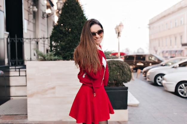 Gracieuse fille aux cheveux longs en jupe rouge à la mode exprimant des émotions positives sincères