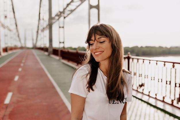 Gracieuse jeune femme aux cheveux longs posant avec plaisir tout en marchant à l'extérieur de bonne humeur.