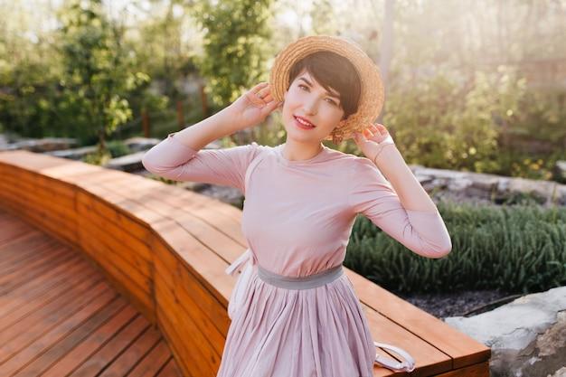 Gracieuse jeune femme en vêtements vintage posant volontiers dans le parc en profitant de la lumière du soleil