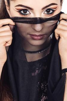 Gracieuse jeune fille danseuse du ventre avec maquillage oriental posant dans un costume de raqs sharqi. femme couvre son visage avec un voile noir. isolé sur blanc