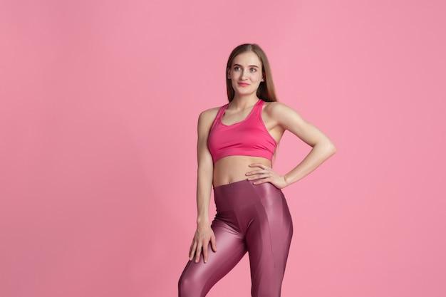 Gracieux. belle jeune athlète féminine pratiquant, portrait rose monochrome. pose de modèle caucasien de coupe sportive. musculation, mode de vie sain, concept de beauté et d'action.