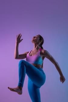 Gracieux. jeune femme sportive s'entraînant isolée sur fond de studio dégradé à la lumière du néon. athlétique et gracieux. sport moderne, action, mouvement, concept de jeunesse. belle femme caucasienne pratiquant.