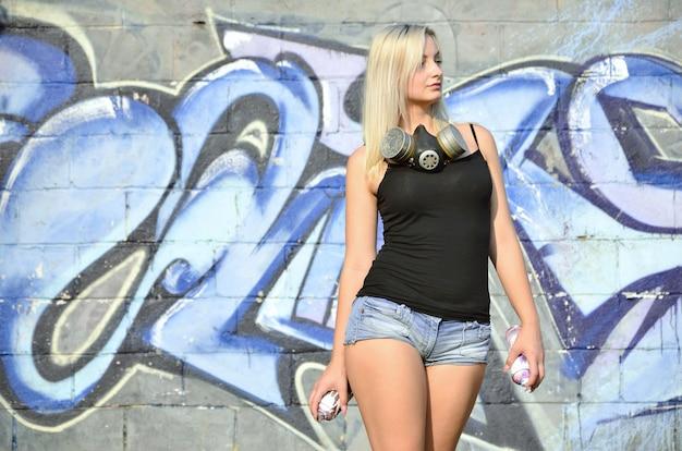 Une graffeuse de fille sexy jeune et belle avec un spray de peinture
