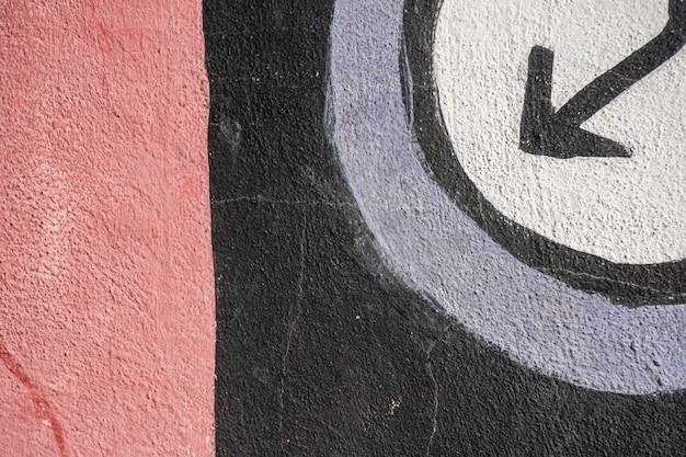 Graffiti inférieur avec flèche et noir sur fond rouge