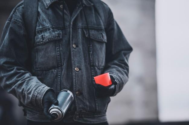 Graffitiste en manteau de denim avec bombe de peinture. préparer un travail