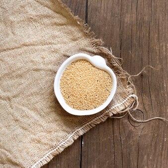 Grain d'amarante biologique brut dans un bol sur la vue de dessus de table en bois