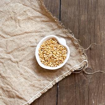 Grain de blé biologique brut grain d'amarante biologique brut dans un bol sur la vue de dessus de table en bois