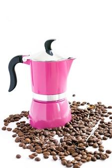 Grain de café, cafetière rose et cuillères sur fond blanc