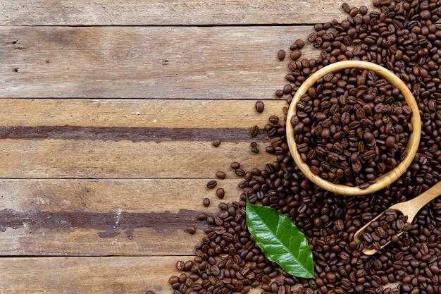 Grain de café dans une tasse blanche sur plancher de bois