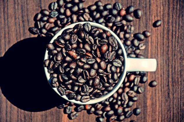 Grain de café dans une tasse sur le bureau en bois - style vintage