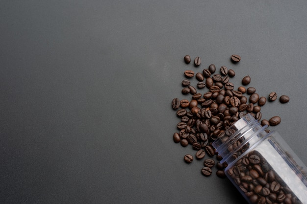 Grain de café sur un fond en bois noir. vue de dessus