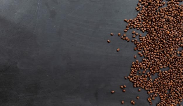 Grain de café sur fond de plancher en bois noir. vue de dessus. espace pour le texte