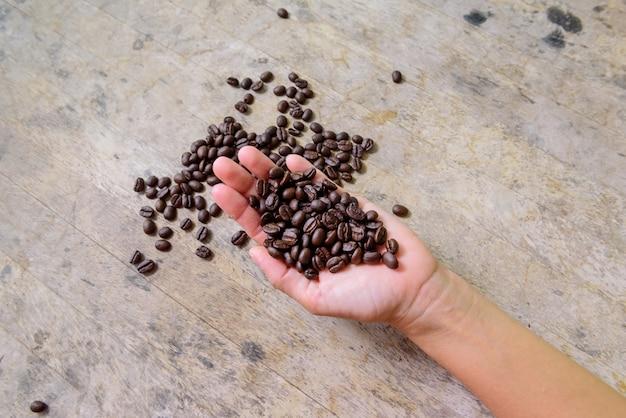 Grain de café à la main sur le vieux bois