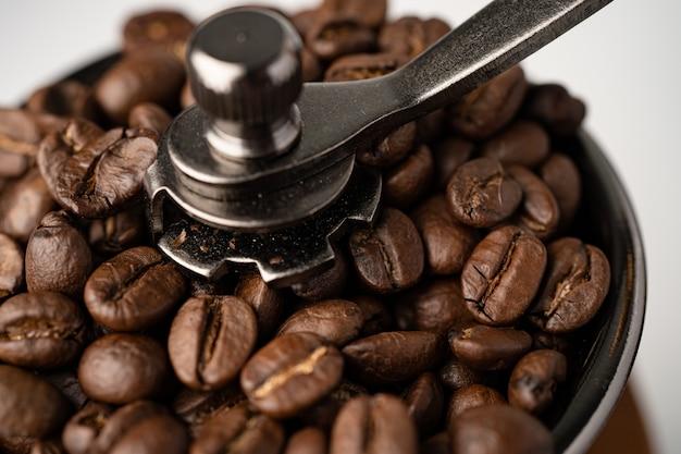 Grain de café torréfié dans un moulin en bois sur fond blanc.