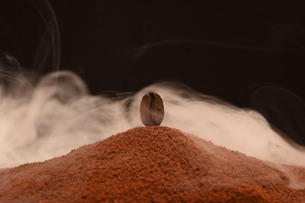 Grain de café torréfié frais se dresse sur une dispersion de café moulu dans la fumée