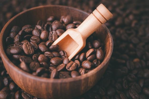 Grain de café torréfié moyen dans un bol en bois.