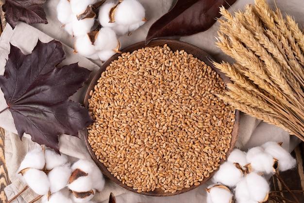Grain et oreilles autour sur du bois rustique près d'une assiette en bois ronde avec des oreilles de blé en coton sec