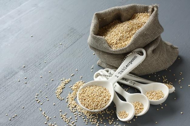 Grain de quinoa dans des cuillères à mesurer en porcelaine sur fond gris